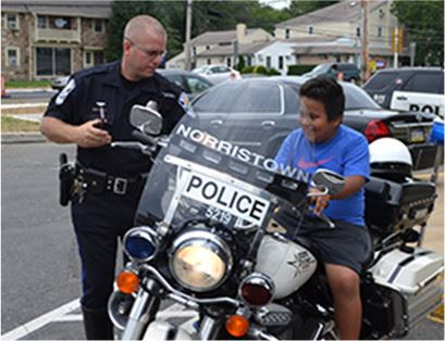 Policeman showing young man his motorcycle