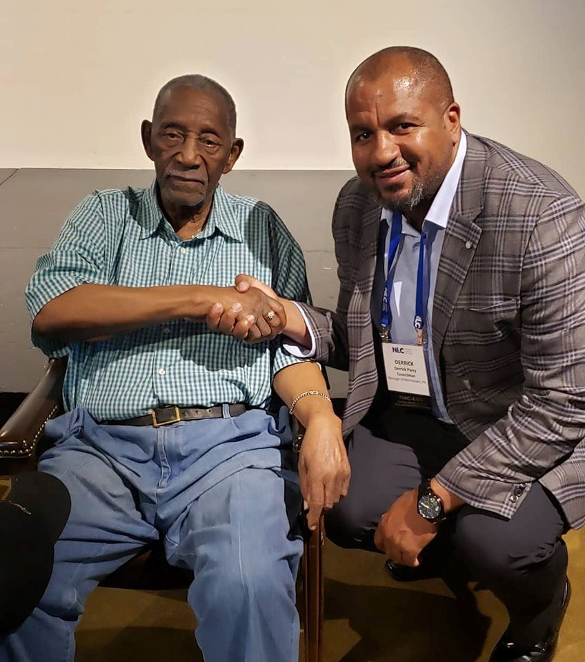 Councilman Derrick Perry shakes the hand of Civil Rights activist Charles Evers